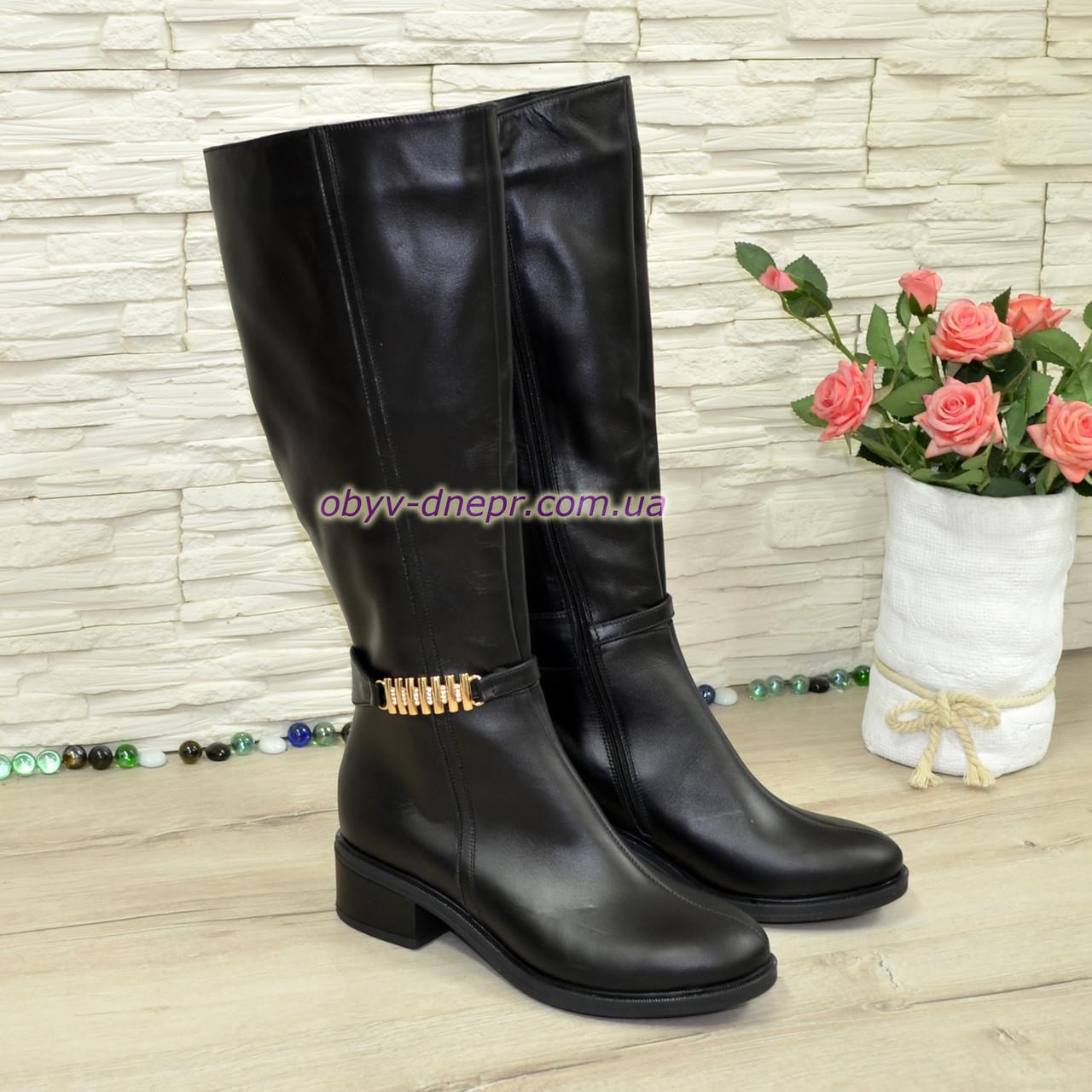 Высокие сапоги зимние кожаные на меху, декорированы лаковым ремешком с фурнитурой.