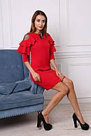 Яркое красное платье украшено украшением на горловине