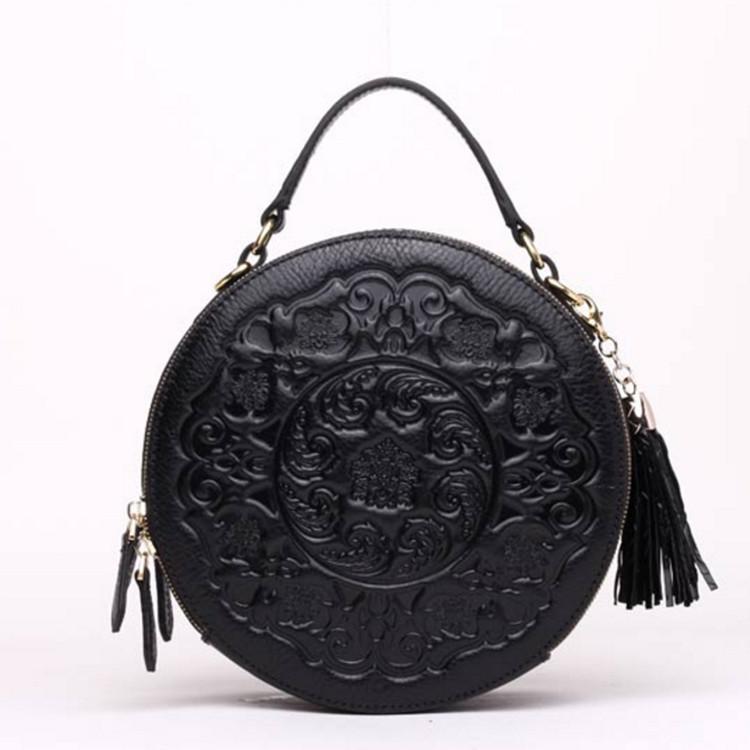 Женская круглая сумка кросс-боди черная кожаная с рисунком и декоративной кисточкой