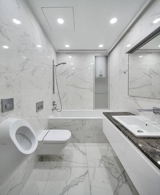 Белая тумба под умывальник со столешницей из натурального камня. Дверь в нише из матового стекла. Зеркало с подсветкой.