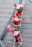 Новогодний декор Bonita Три фигуры Деда Мороза по 25 см ползут на лестнице