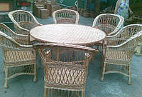 Плетеной набор из шестьма стульями и круглым столом.
