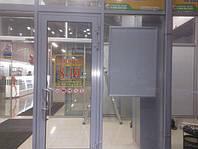 Информационные таблички на входных дверях в торговый центр. По бокам дополнительно установлены рамки с клик-системой для быстрой и частой смены изображений
