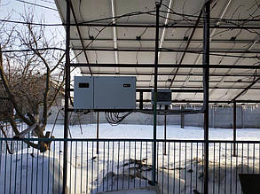 Солнечный инвертор и шкаф защиты, навешенные на опорах металлоконструкции.