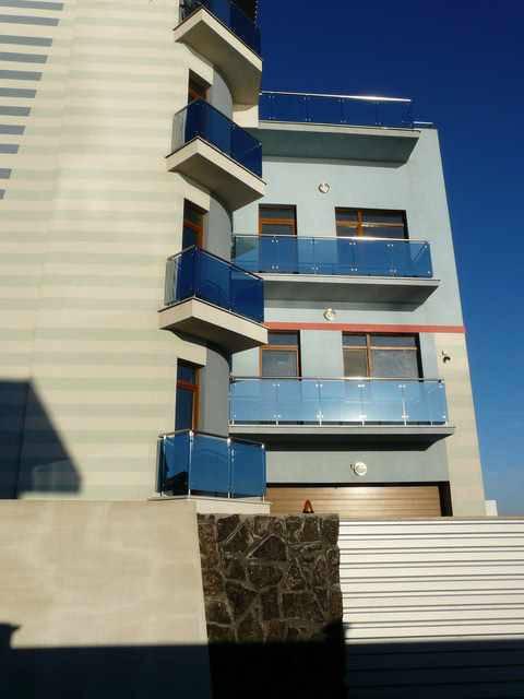 """Балконы: нержавеющая сталь, закаленное стекло марки """"Lake Blue""""."""