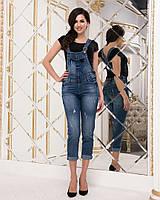 Женский джинсовый комбинезон с подкатом на брюках и потертостями