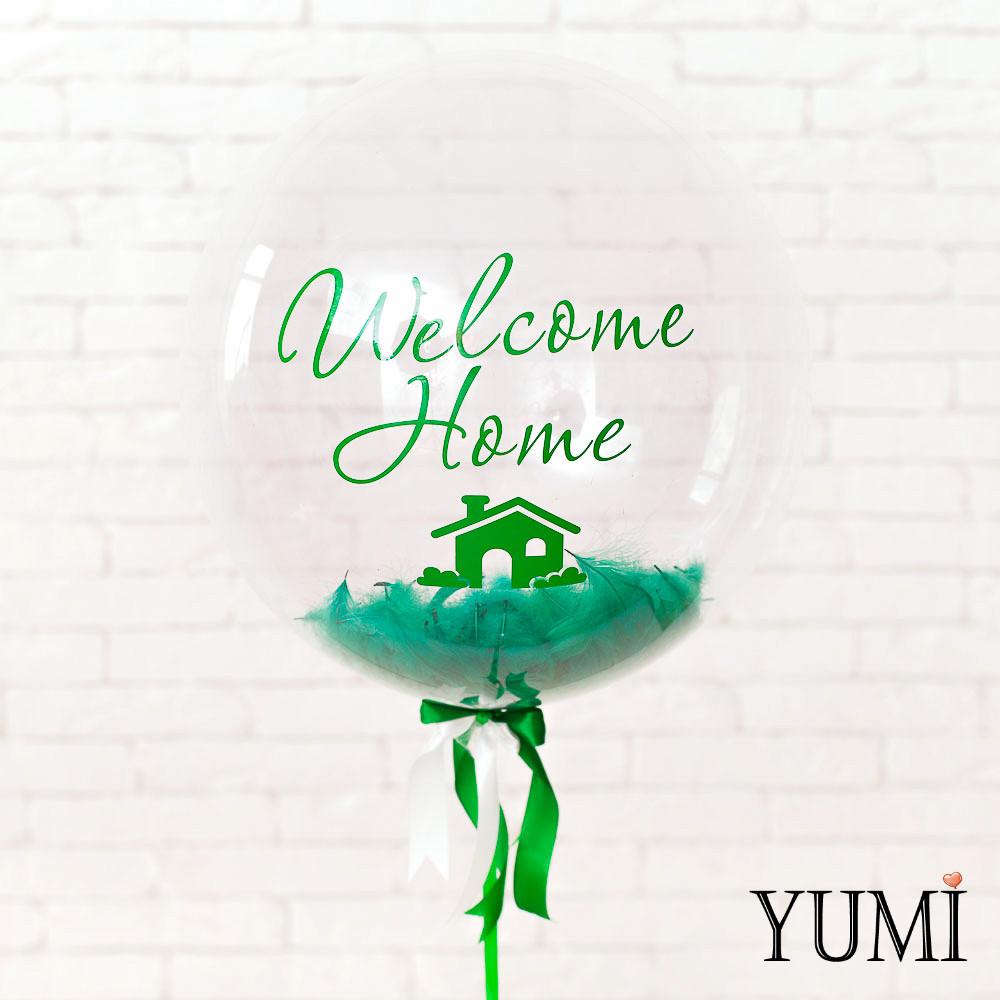 Композиция: Шар с гелием Bubble с зеленой надписью Welcome Homе, зелеными перьями на зеленой атласной ленте