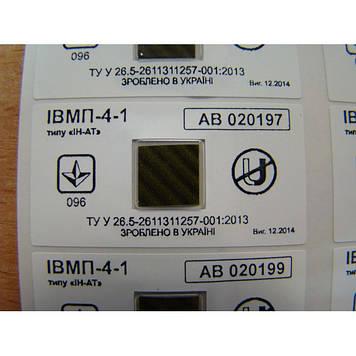 """Индикатор магнитного поля ИВМП 4-1 типа """"ИН-АТ"""" на белой пломбировочной пленке."""