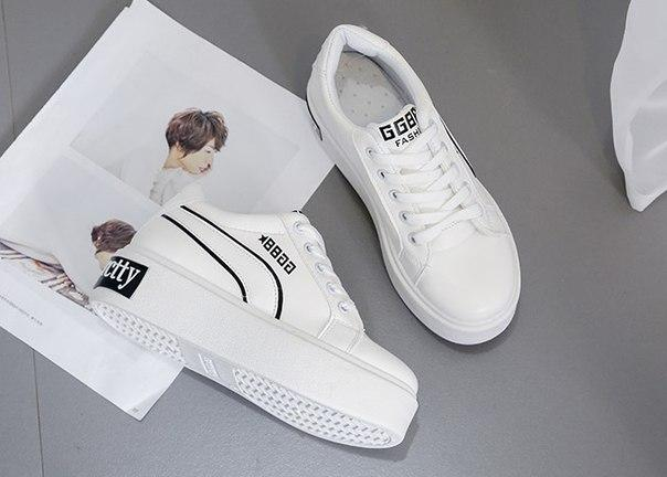 Белые кроссовки на высокой подошве с черной надписью