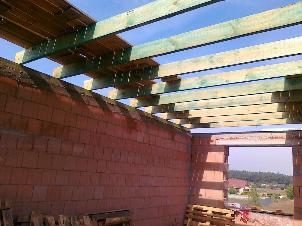Вот уже и второй этаж перекрываем деревянными балками. К работе приступили кровельщики.