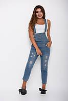Синий джинсовый комбинезон с дырками и потертостями