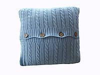 Стильная серо-голубая вязанная косичками наволочка.