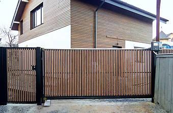 Откатные ворота и калитка с двусторонним вертикальным заполнением лиственницой (шахматка). Использована фурнитура для откатных ворот Rolling Center (Италия)