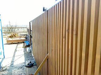 Каркас откатных ворот заполеннный деревянным штакетником.