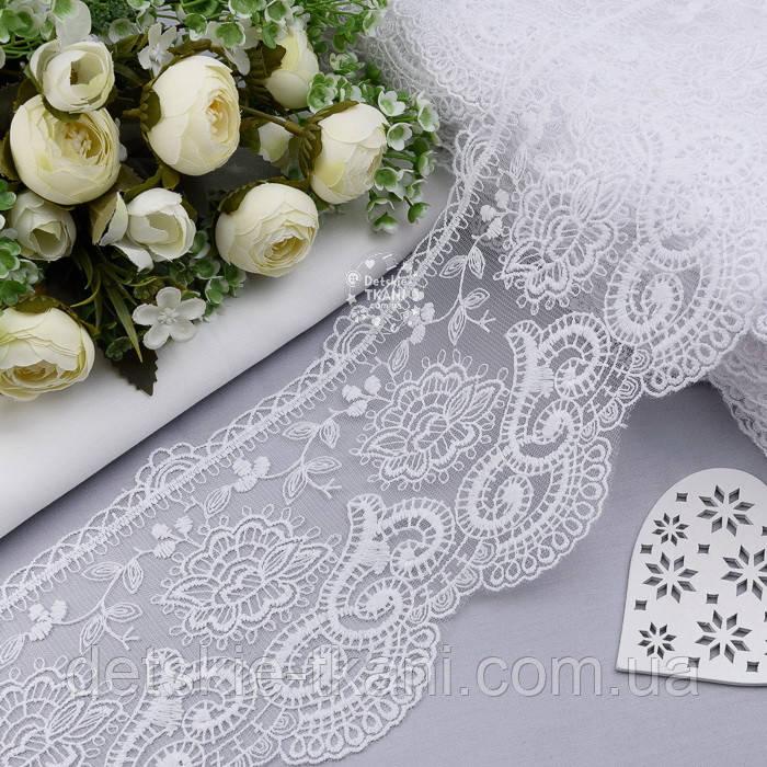 Кружево белого цвета с пышным цветком и завитками, ширина 13 см.