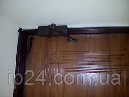 Фото установленного дверного доводчика Geze (в коричневом цвете) на металлической двери