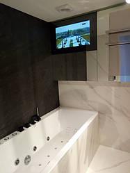 Влагозащищённый телевизор установлен в ванной комнате