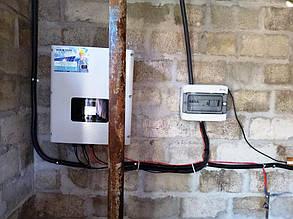 Сетевой инвертор и шкаф защиты, навешенные на стене в сарае.