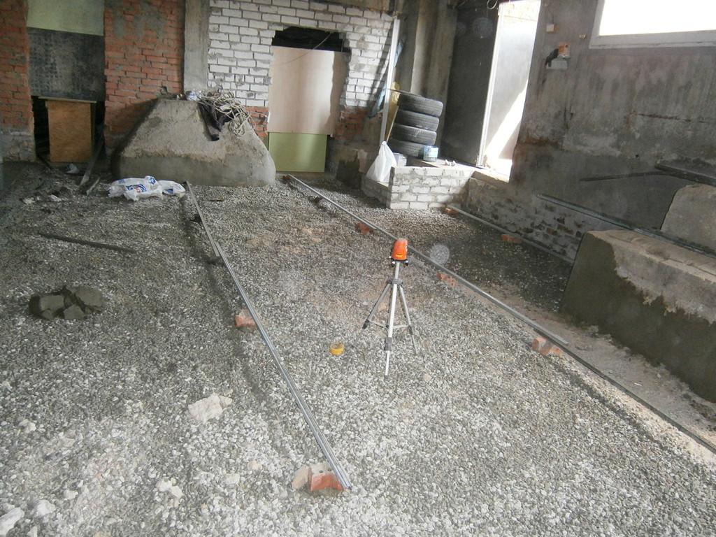 Изготовление бетонного пола в подвале. Силами заказчика был демонтирован старый пол. Нашими усилиями выполнена планировка щебнем, установка маяков (к сожалению, бюджет не предусматривал армирования, поэтому использовали фибробетон).