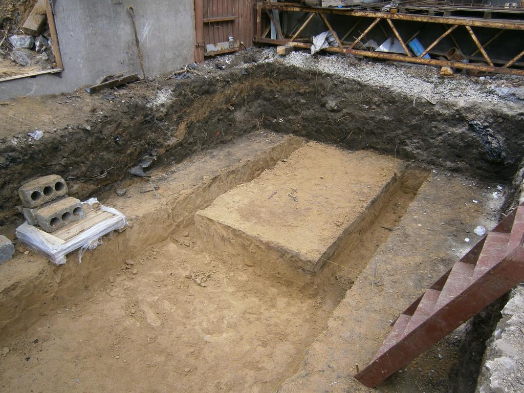 Размер первоначального котлована - 7*5*1.2 м. Затем внутри были вырыты две траншеи под ленточный фундамент и основная яма (1.5*2 и ещё на 4 м в глубину). Весь грунт сразу же насыпался в вёдра и выносился за территорию (через отверстие в заборе).