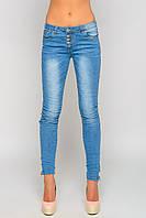 Женские джинсы прилегающего кроя, застегиваются на ряд пуговиц, местами выбелены, низ штанин застегивается на