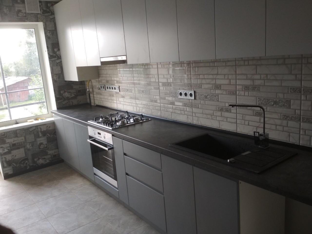Кухня серая, верх белый, фасады без ручек.