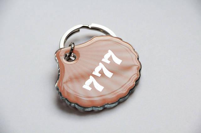 Брелок для ключей в виде раковины. На каждый брелок нанесен номер комнаты.
