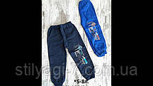 Спортивные штаны для мальчика на 5-8 лет синего цвета с надписью на манжете оптом