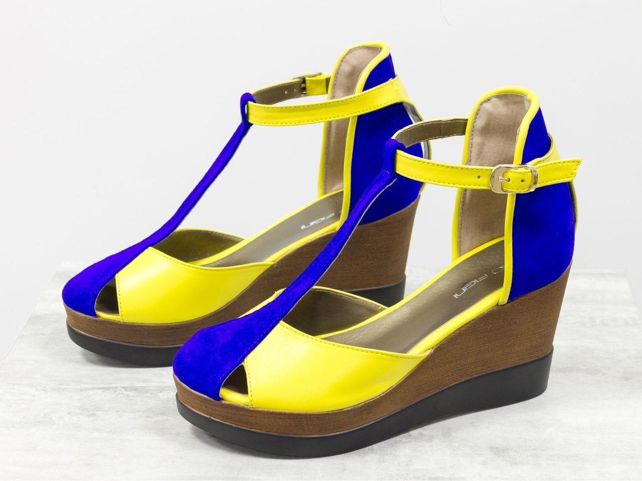 Яркие босоножки из натуральной кожи желтого цвета и ярко-синей замши с контрастной отстрочкой на устойчивой танкетке черно-коричневого цвета,