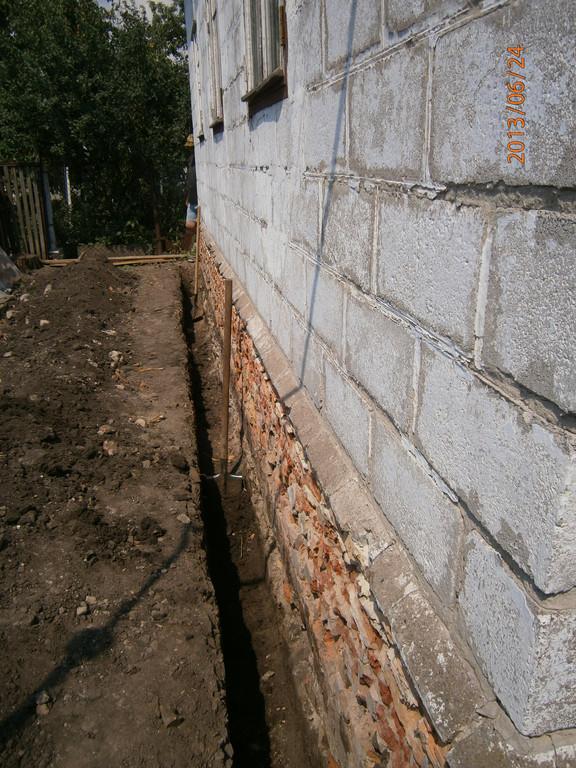 Траншея вдоль стены дома под устройство фундамента для облицовки кирпичом (облагораживание старого строения). Район проспекта Металлургов.
