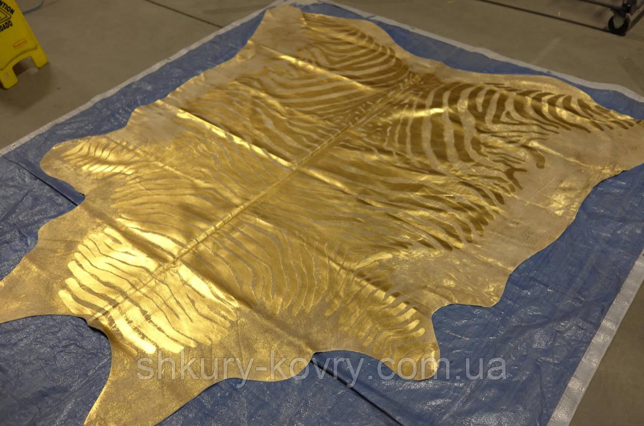 Кожа коровы золотого цвета с золотым рисунком зебры