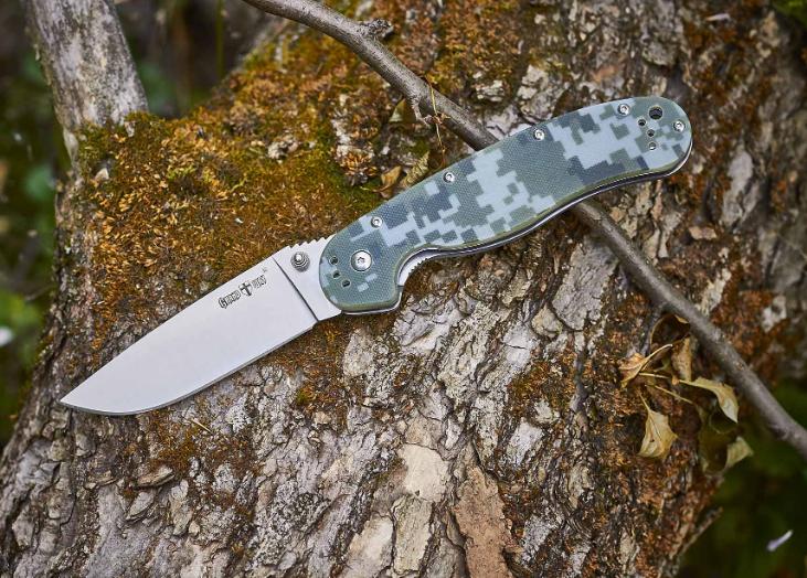 Нож складной, ощутимо увесист, камуфляжной расцветки, с длинной рукояткой из композита G10, на каждый день