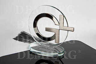 Награда из стекла с металлическими элементами.