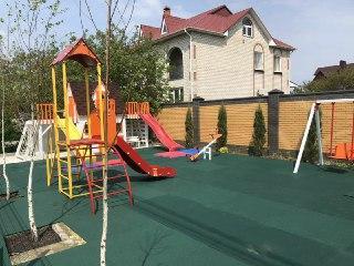 Детская площадка во дворе частного дома.