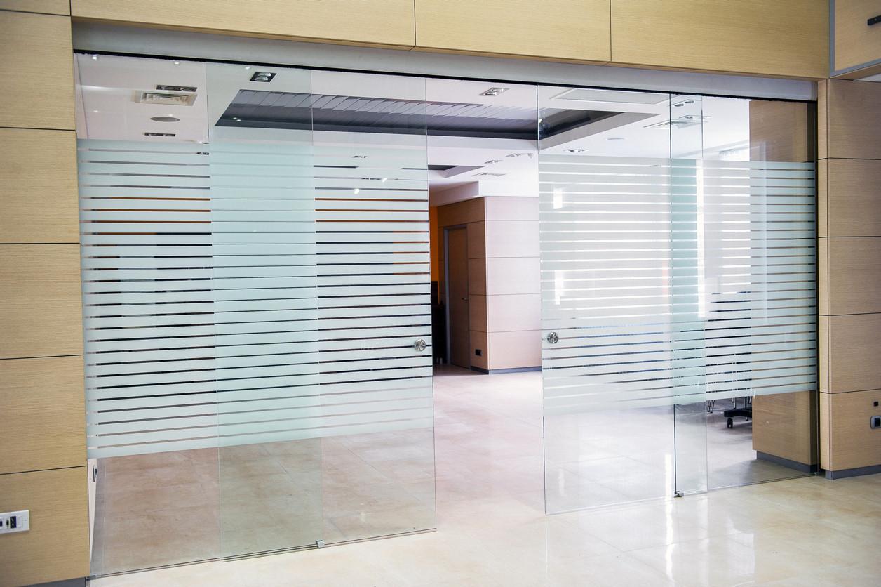 6 Раздвижная перегородка из стекла с наклеенной пленкой белыми полосами в офисе