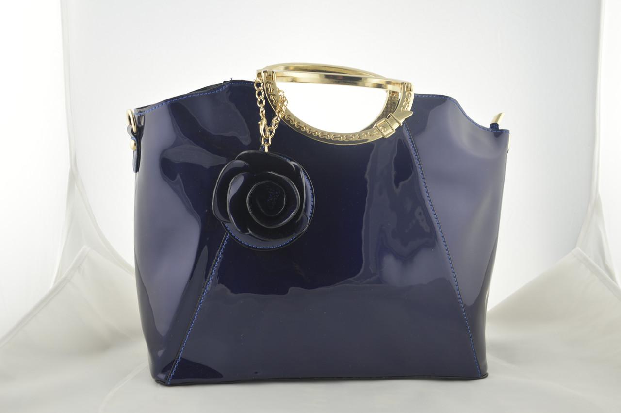 Лаковая синяя большая женская сумка держит форму