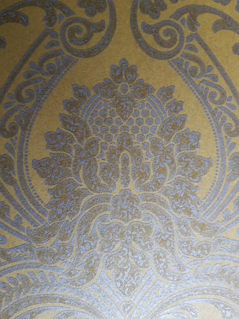 Обои флизелиновые  Khroma Serenade SER208 вензеля розетки завитки золотом на желтом фоне