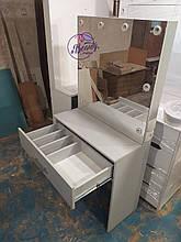 Неширокий гримерный стол с центральным ящиком, зеркало без рамы.