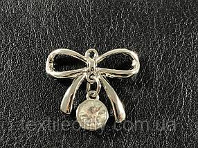 Пришивная металлическая эмблема бантик серебро 26х22 мм