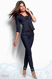 Женским костюм с приталенным жакетом и облегающими брюками в деловом стиле темно-синий