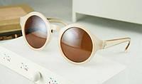 Солнцезащитные круглые очки, оправа однородной фактуры, душки из прозрачного пластика светло-бежевого цвета