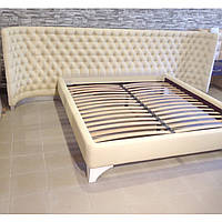 """Кровать """"Impreza"""" с мягким гнутым изголовьем в ромбах и пуговицах."""