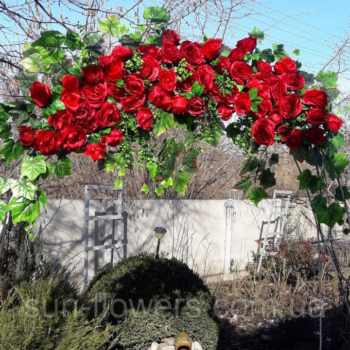 Кущ в'ється червоної троянди штучною.
