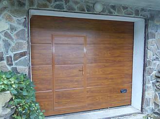 Секционные гаражные ворота Ритерна со встроенной калиткой в цвете золотой дуб с гладким типом полотна SLICK.