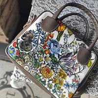 Стильная женская сумка-чемодан с цветочным принтом.