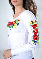 Нарядная женская вышиванка в белом цвете украшена насыщенным цветочным принтом