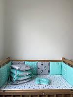 Комплект бортики на 4 стороны кроватки со съёмными наволочками, простынка на резинке, ортопедическая подушка.
