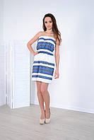 Праздничное женское платье украшено этнической вышивкой с синим орнаментом