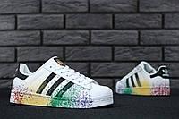 Белые женские кеды из кожи с разноцветными пятнами краски и черными полосами Adidas Superstar