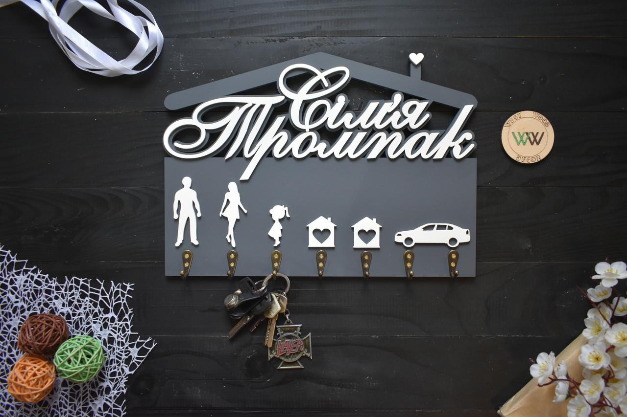Деревянная ключница в виде домика с фамилией и большими крючками для каждого члена семьи и машины